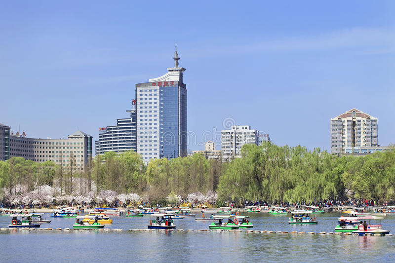 Kunming Lake at Yuyuantan Park with buildings on background, Beijing, China. BEIJING-MARCH 30, 2014. Yuyuantan Park Kunming Lake with view on Beijing Skyline royalty free stock photo