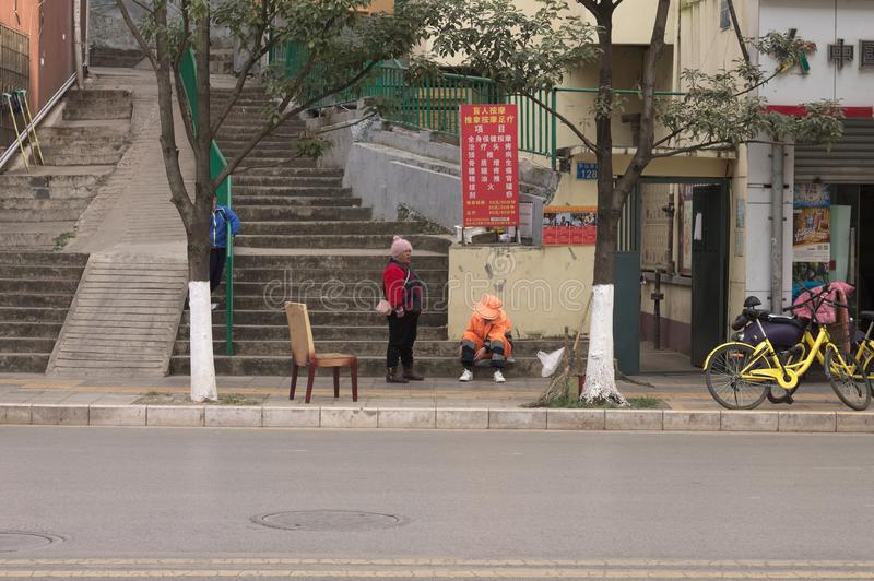 Two chinese women on the sidewalk with a chair royalty free stock images