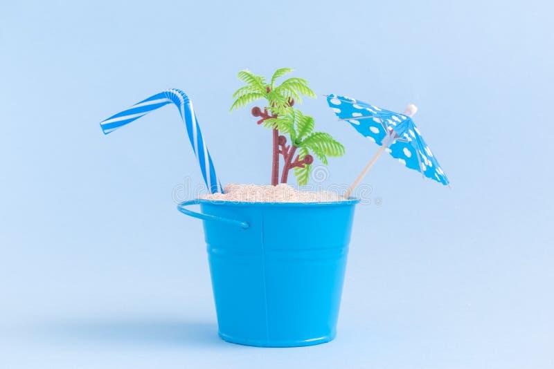 Kunna med sand och plast-palmträdet som isoleras på blå bakgrund, dricka sugrör, det pappers- coctailparaplyet Sommartidsemesterk royaltyfri bild