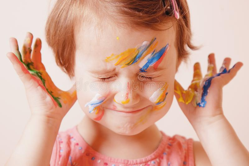 Kunst, creatieve en gelukkinderjarenconcept Sluit omhoog kleurrijk geschilderd handen en gezicht in een mooi klein kindmeisje stock fotografie