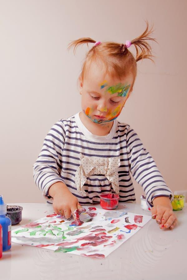 Kunst, creativiteit, kinderjarenconcept Weinig leuk kindmeisje die met kleurrijke handen schilderen stock fotografie