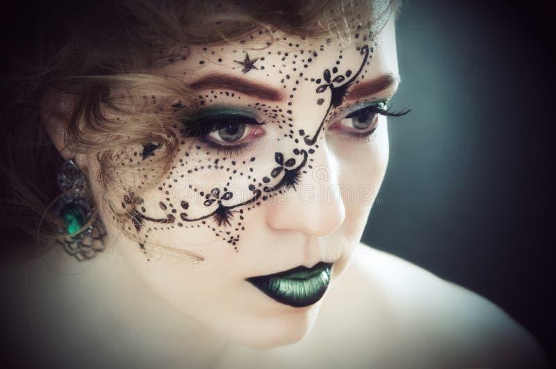 Kunst, een meisje met een beeld op haar gezicht stock foto's