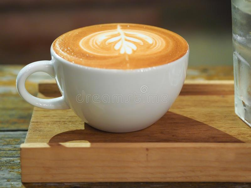 Kunst Latte ist auf hölzerner Untertasse lizenzfreies stockfoto