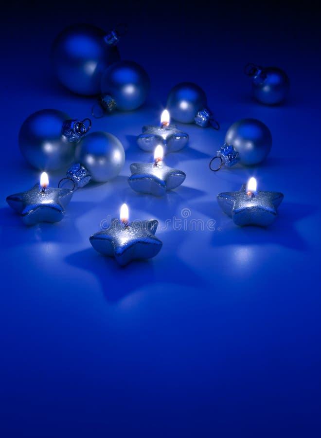Kunst-Weihnachtskerzen auf einem blauen Hintergrund stockfotografie