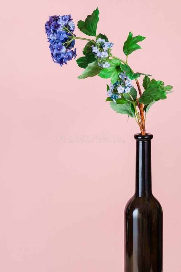 Kunstbloem in een bruine glazen fles op een roze royalty-vrije stock afbeelding