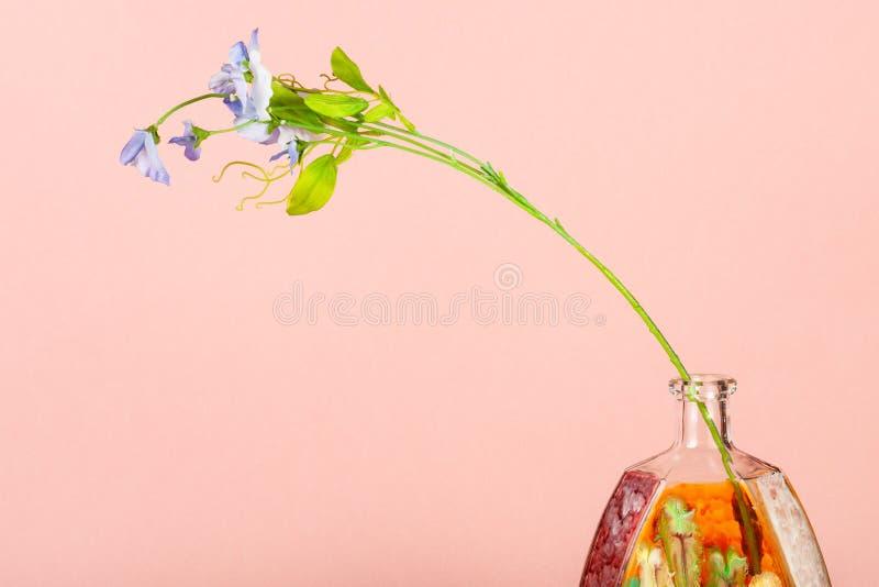 Kunstbloem in handbeschilderde fles op perzik royalty-vrije stock foto's