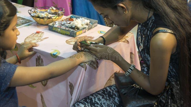 Kunstenaar die hennatatoegering op kindhand toepassen stock afbeeldingen