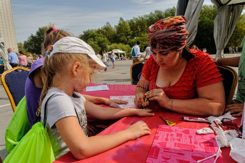 Kunstenaar die hennatatoegering op meisjeshand toepassen Tyumen stock fotografie