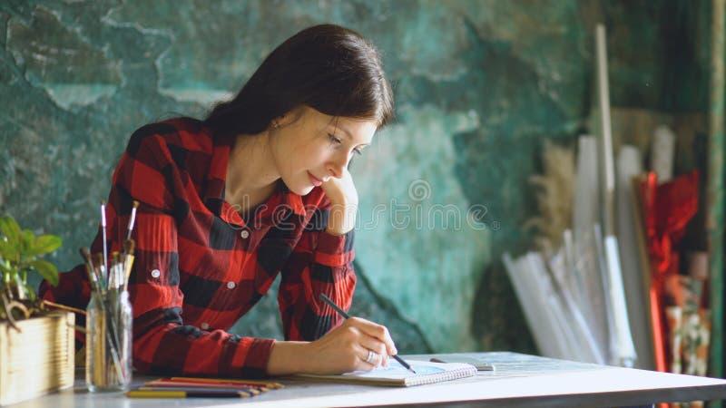 Kunstenaar die van de portret de jonge vrouw scetch op document notitieboekje met potlood schilderen stock afbeelding