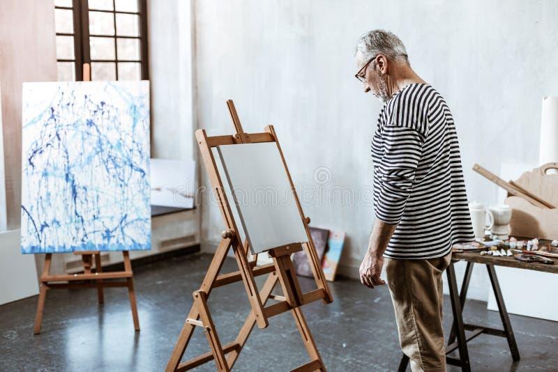 Kunstenaar die zich voor wit canvas bevinden die geen inspiratie hebben stock fotografie