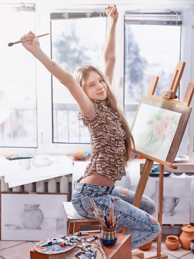 Kunstenaar het schilderen op schildersezel in studio Meisjesverven met borstel stock afbeelding