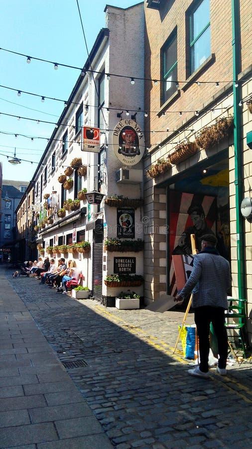 Kunstenaar op een straat in Belfast stock afbeeldingen