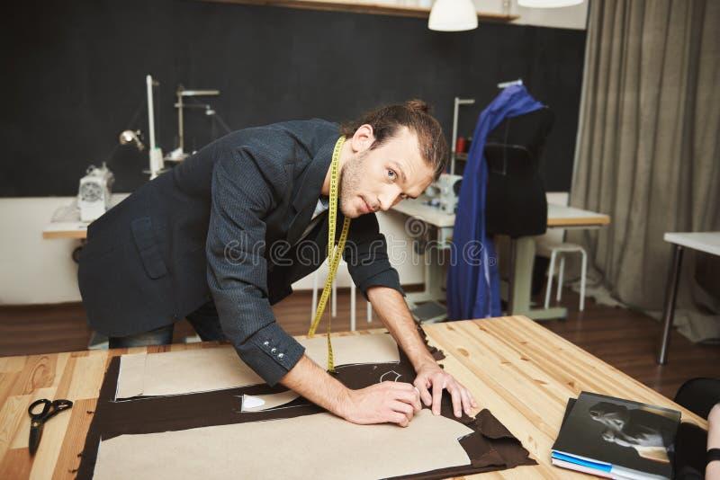 Kunstenaar in studio Sluit omhoog van begaafde aantrekkelijke jonge mannelijke manierontwerper die bij de nieuwe de winterinzamel stock foto