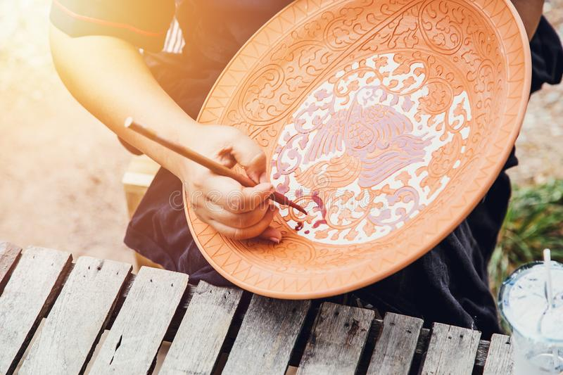 Kunstenaarshand het schilderen aardewerk met traditionele sukhothai styel stock fotografie