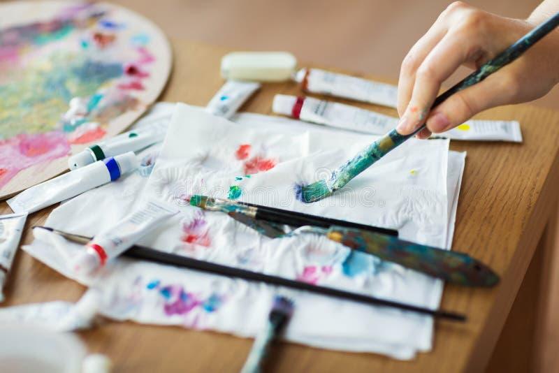 Kunstenaarshand met penseel, document en verfbuizen royalty-vrije stock foto's