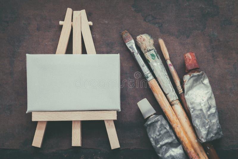 Kunstenaarspenselen, verfbuizen en kleine schildersezel met canvasclose-up Hoogste mening stock foto's