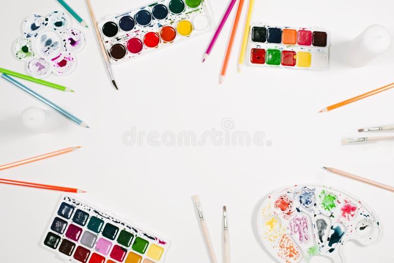 Kunstenaarswerkruimte met waterverf, kleurenpotloden, palet en borstels bij witte achtergrond Vlak leg, hoogste mening royalty-vrije stock foto's