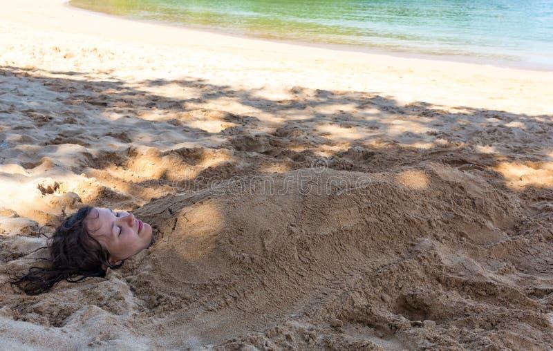 Kunstfoto van mooie die dame in het zand wordt begraven royalty-vrije stock afbeelding