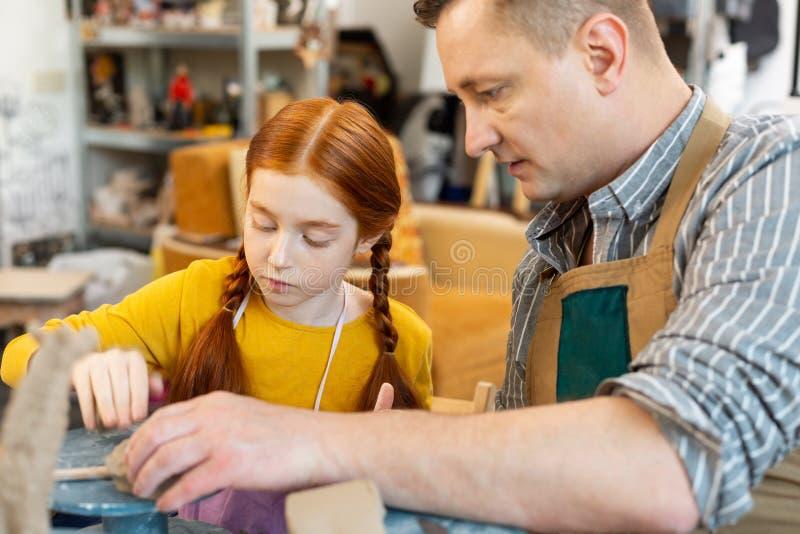 Kunstlehrer, der seinen anziehenden rothaarigen Sch?ler unterst?tzt lizenzfreie stockbilder