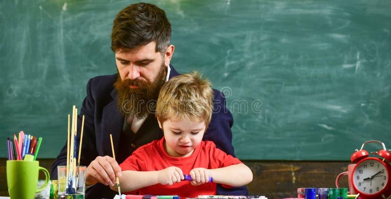Kunstles bij kleuterschool Leraar die de jongen helpen om beeld tot stand te brengen Mens het schilderen met lange borstel terwij royalty-vrije stock foto
