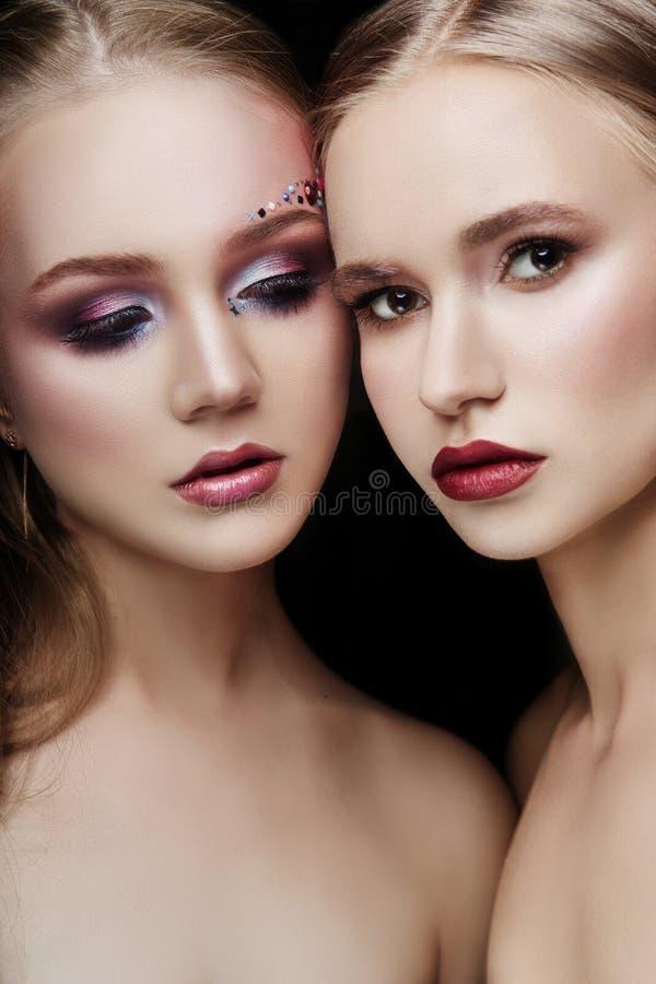 Kunstmake-up zwei umarmende Mädchen, viele Bergkristalle von verschiedenen Formen, glatte Hautpflege des schönen Gesichtes Schönh lizenzfreie stockfotografie