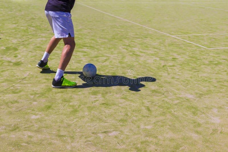 Kunstmatig gras in het zand Voetbalwedstrijd voor kinderen Opleiding en voetbal voetbaltoernooien Benen in tennisschoenen en royalty-vrije stock foto