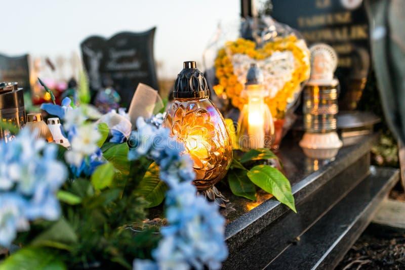 Kunstmatige en echte bloemen en aangestoken kaarsen die op de grafsteen in de begraafplaats liggen stock fotografie