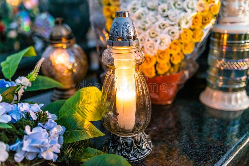 Kunstmatige en echte bloemen en aangestoken kaarsen die op de grafsteen in de begraafplaats liggen stock foto