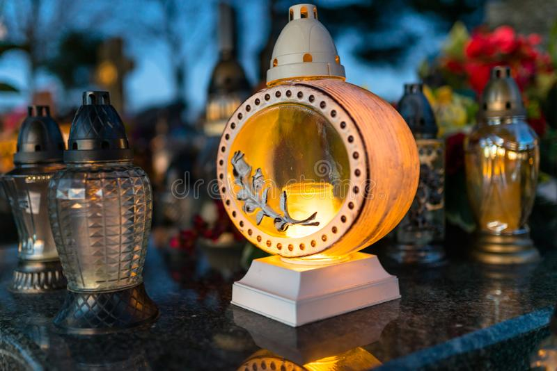 Kunstmatige en echte bloemen en aangestoken kaarsen die op de grafsteen in de begraafplaats liggen stock foto's