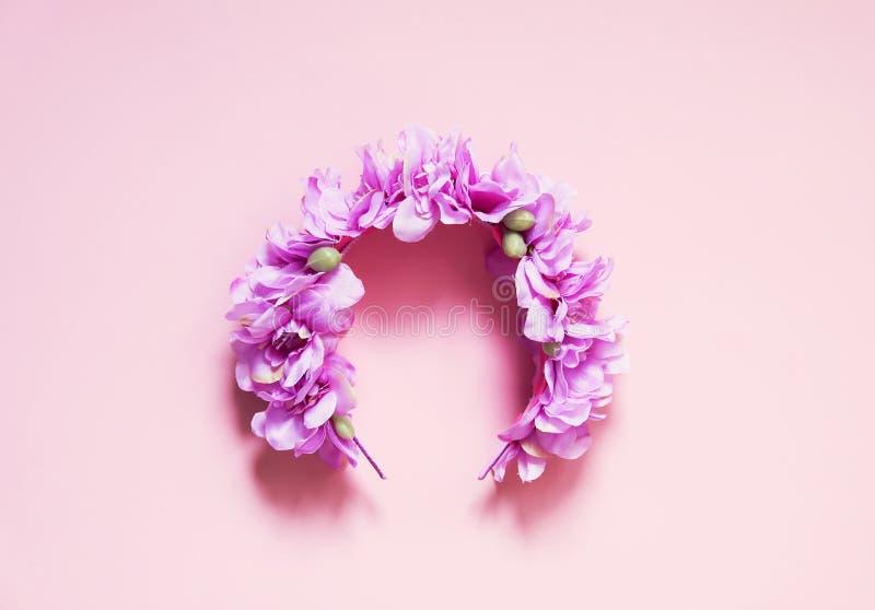 Kunstmatige kroon van purpere bloemen op roze achtergrond met exemplaarruimte stock afbeelding