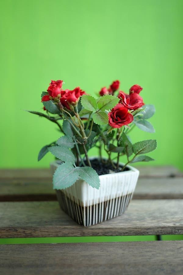 Kunstmatige rode rozen op houten lijst met groene achtergrond royalty-vrije stock fotografie