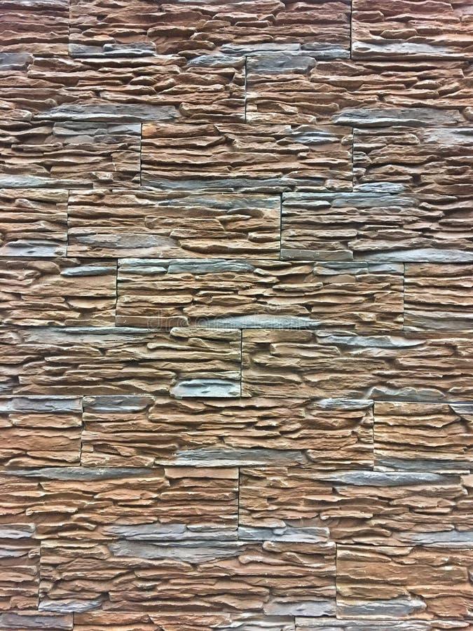 Kunstmatige steen Decoratieve muur van kunstmatige gescheurde steen Steenmetselwerk in geometrisch patroon als achtergrond of tex royalty-vrije stock afbeeldingen