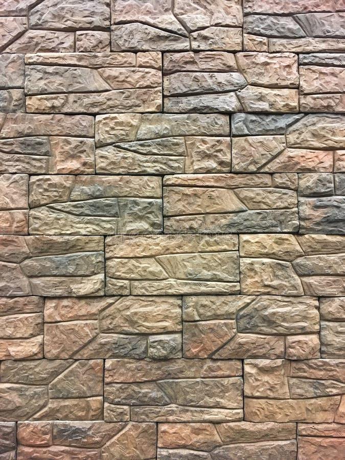 Kunstmatige steen Decoratieve muur van kunstmatige gescheurde steen Steenmetselwerk in geometrisch patroon als achtergrond of tex stock afbeelding