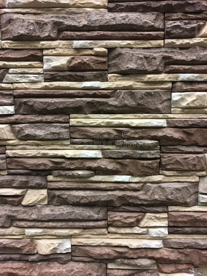 Kunstmatige steen Decoratieve muur van kunstmatige gescheurde steen Steenmetselwerk in geometrisch patroon als achtergrond of tex stock foto