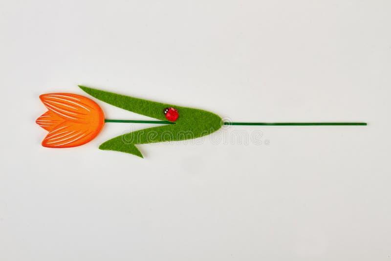 Kunstmatige tulp met geïsoleerd onzelieveheersbeestje stock foto