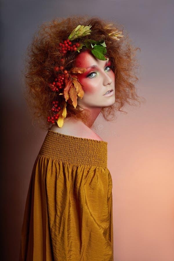 Kunstporträt des Frauenherbstes in ihrem Haar, klaren Fallfarben und -make-up, rotes gelocktes Haar und umfangreiches Haar Blätte lizenzfreie stockfotos