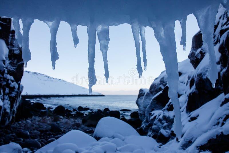 Kunstrahmen von kalten Eiszapfen des weißen Schnees auf Spitzenvordergrund- und Steinstrand von Nordnordpolarmeer mit schneebedec lizenzfreie stockbilder