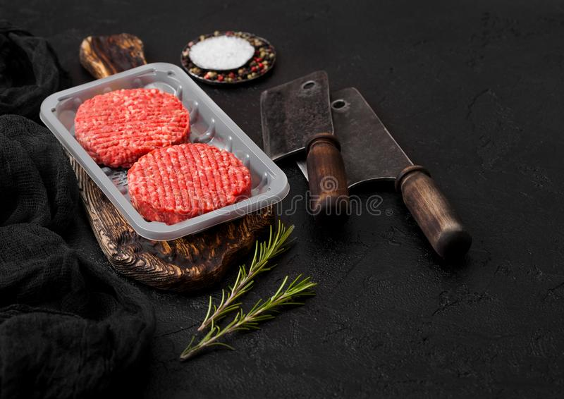 Kunststoffschale mit rohen gehackten selbst gemachten Landwirten grillen Rindfleischburger mit Gew?rzen und Kr?utern und Fleischb lizenzfreies stockbild
