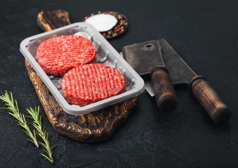 Kunststoffschale mit rohen gehackten selbst gemachten Landwirten grillen Rindfleischburger mit Gew?rzen und Kr?utern und Fleischb stockfotografie