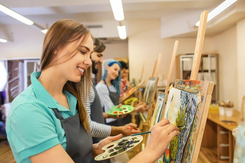 Kunststudenten die in workshop schilderen stock fotografie