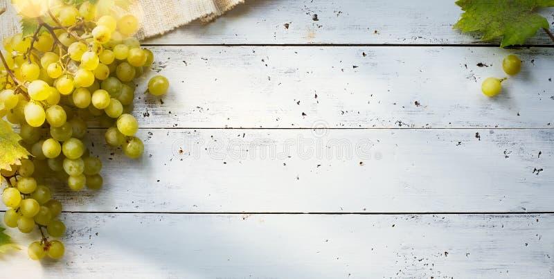 Kunsttrauben auf weißer Tabelle; Gewürzweinberghintergrund stockfoto