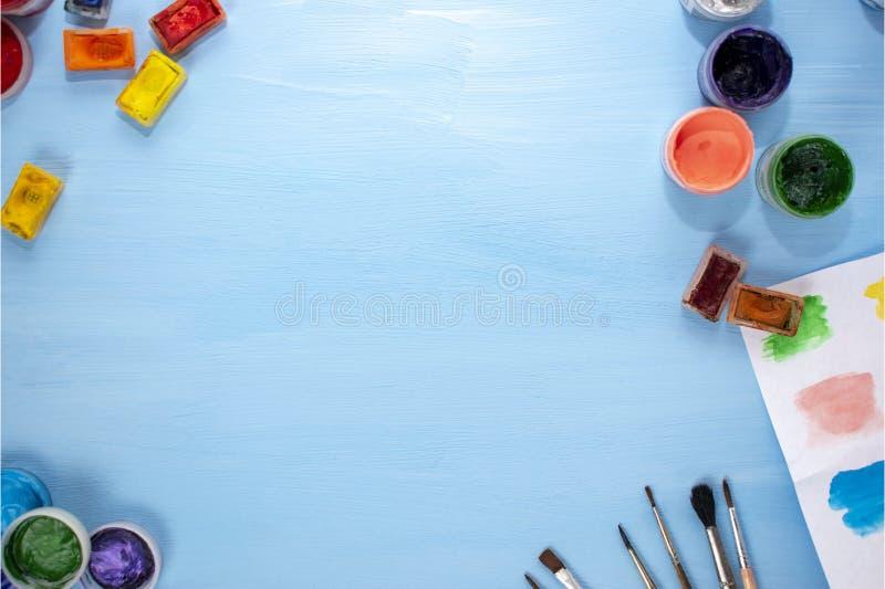 Kunstversorgungen: Aquarell, Acryl, Bürsten und Palette auf einem blauen Hintergrund Flache Lage, Draufsicht Schreibtischkünstler lizenzfreies stockfoto