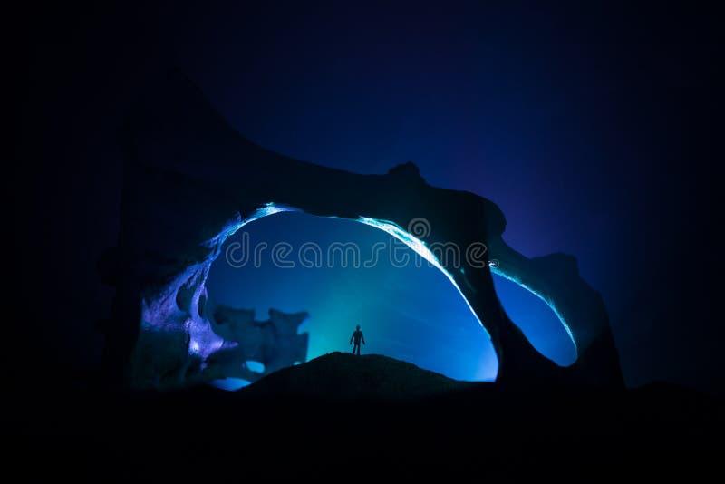 Kunstwerkdecoratie met dierlijk been Silhouet in een ondergrondse verlaten crypt Mens die zich voor een holingang bevindt stock fotografie