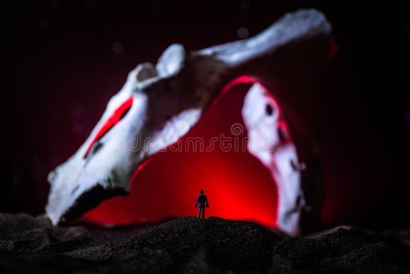 Kunstwerkdecoratie met dierlijk been Silhouet in een ondergrondse verlaten crypt Mens die zich voor een holingang bevindt stock afbeeldingen
