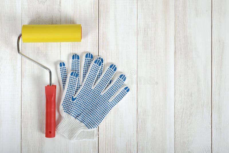 Kunstzusammensetzungsaufmachung von den Handschuhen und von Rolle, die auf weißer Holzoberfläche liegen lizenzfreies stockbild