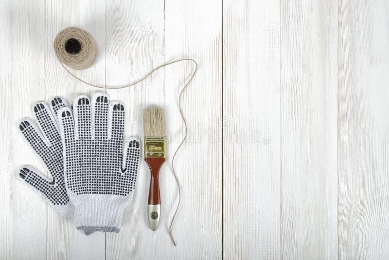 Kunstzusammensetzungsaufmachung von den Handschuhen, von Bürste und von Schnur, die auf weißer Holzoberfläche liegen lizenzfreie abbildung