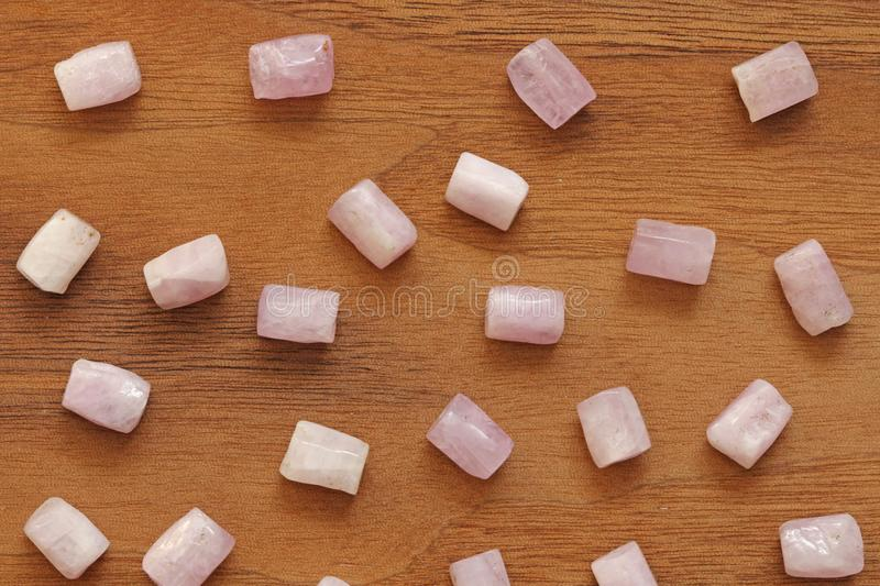 Kunzite is a natural pink stone for creating Jewelry on a natural wooden background. Natural crystals of pink and lilac stones royalty free stock image