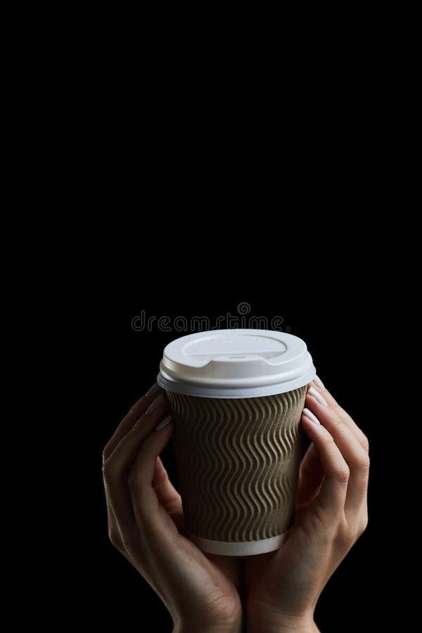 Kup kobiecej dłoni trzymającej filiżankę kawy na ciemnym tle obrazy royalty free