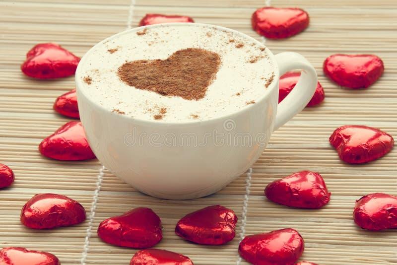Kupa av kaffe med den hjärtasymbol och godisen omkring. royaltyfri foto