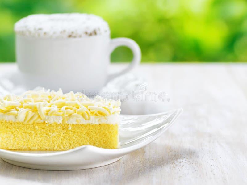 Kupa av kaffe och den nya tårtan royaltyfri fotografi